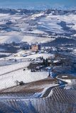 Snowy hilly landscape on the vineyards of the Langhe in the Unesco territory of Italy royalty free stock image