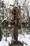 Snowy historic Jesus on winter old Prague Cemetery, Czech Republic Royalty Free Stock Images