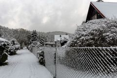 Snowy huts and a footpath around a fence. In the winter landscape royalty free stock photos