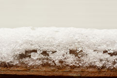 Snowy ice on wood beam Royalty Free Stock Image