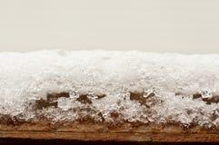 Snowy ice on wood beam. Snowy ice on outdoor wood beam Royalty Free Stock Image