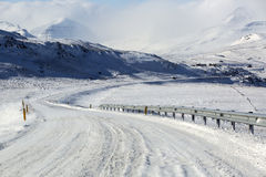 Snowy and icy road with volcanic mountains in wintertime Stock Images