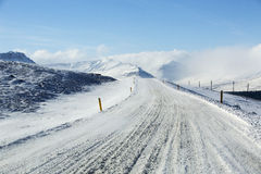 Snowy and icy road with volcanic mountains in wintertime Royalty Free Stock Photography