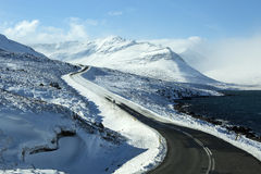 Snowy and icy road with volcanic mountains in wintertime Royalty Free Stock Photo