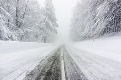 Snowy and icy road in foggy weather royalty free stock photos