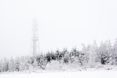 Snowy and icy tower on a hill in the middle of forests Royalty Free Stock Photography