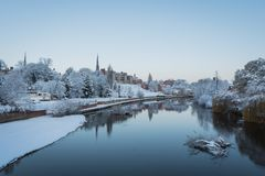 Snowy, icy view along the River Severn, Shrewsbury, Shropshire. View along the River Severn from the English Bridge in Shrewsbury with a reflection in the river Stock Photo
