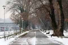 Snowy idyll in the park. With trees and bench Stock Image