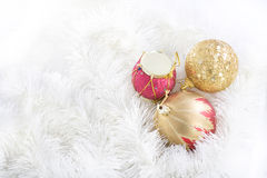 Snowy Jazz. Golden and Golden-red Christmas balls and red drum-toy lying in a white garland Royalty Free Stock Photos