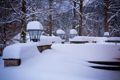 Snowy lamps near house in the woods Royalty Free Stock Images
