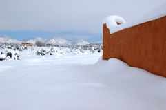 Snowy Landscape. Snowfall in the southwest including an adobe wall and mountains in the distance stock image