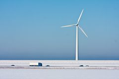 Snowy landscape with awindturbine and a highway Stock Photos
