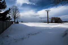 A snowy landscape with a cross under a tree and a pole with an electric lead Stock Photos