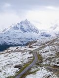 Snowy landscape with gravelly road. Misty sharp peaks of  high mountains in background. Royalty Free Stock Photography