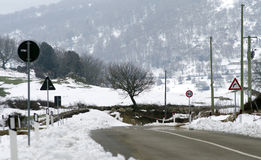 Snowy landscape mountains, road signs, trees, cleaned road. For winter iusses stock images