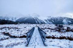 Snow landscape with foot steps over bridge in New Zealand. stock photo