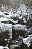 A snowy landscape with a stream, large stones and snow covered trees Stock Photo