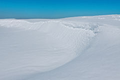Snowy-Landschaft mit Flussufer an einem sonnigen Windentag Stockfotografie