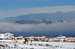 Snowy-Landschaft mit Stadt, Gebirgsdem schwimmen und den Wolken Lizenzfreie Stockfotos