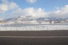 Snowy-Landschaft und -berge unter einem blauen Himmel Stockbild