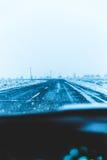 Snowy-Landstraße von einem Fahrergesichtspunkt Stockfoto