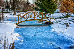 Snowy little bridge over pond 2. Winter in the park. Snowy, wooden bridge over frozen pond. Poland Royalty Free Stock Photography