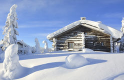 Snowy log cabin in Lapland Finland. Cottage on snowy mountain on a sunny cold winter day in Lapland Finland. Cottages and spruce trees are covered by heavy snow Royalty Free Stock Images