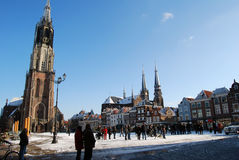 Snowy main square of delft in the Netherlands in the morning wit. H people and blue sky as lifestyle stock photos