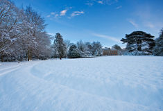 Snowy manor house grounds on a winter afternoon Stock Images