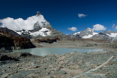 Snowy Matterhorn with clouds and glacier lake Stock Photo