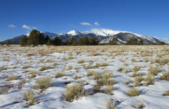 Snowy Meadow with Mountain Background Stock Photos