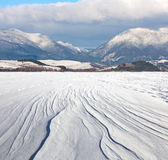 Snowy meadow under mountains Royalty Free Stock Photo