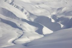 Snowy meandering mountain topography, shades of white and blue.  stock photo