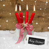 Snowy Merry Christmas : four red burning candles with bow and me Stock Images
