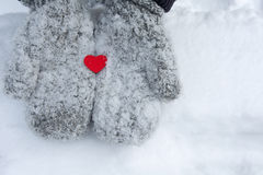 Snowy mittens with tiny red heart Stock Photo