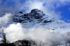 Snowy mountain with low clouds stock photography