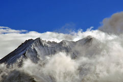 Snowy mountain with cloud coverage and blue sky Stock Photo
