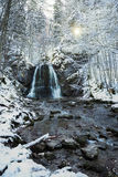 Snowy mountain creek with cascade Stock Images