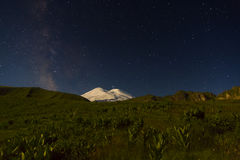 Snowy mountain Elbrus in moonlight, Milky Way stars and Saturn at night Royalty Free Stock Photo