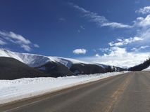 Desolate Snowy Mountain Highway. A highway outside Winter Park, Colorado with snow capped mountains in the distance Stock Images