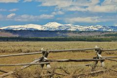 Snowy Mountain Landscape. Snow-covered mountains with a rustic fence in the foreground Stock Photos