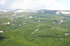 Snowy mountain meadows. Photo of green meadows in the mountains with snow and cloudy sky above them Stock Photography