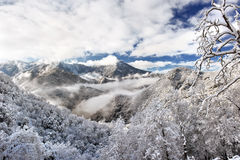 Snowy Mountain Morning. Morning mist and clouds cling to the high mountains stock image