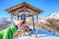Snowy mountain panorama, hand holding an GPS receiver.  Royalty Free Stock Images