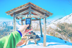 Snowy mountain panorama, hand holding an GPS receiver. Filter applied Stock Photos
