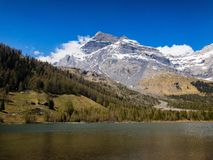 Snowy mountain peak behind an alpine lake. Stock Image