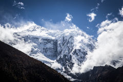 Snowy mountain peak and clouds, Himalaya, Nepal. View from the trekking at Annapurnas circuit, Himalaya, Nepal Royalty Free Stock Photo