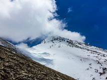 Snowy mountain peak in the clouds royalty free stock images