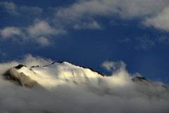 Snowy mountain peak, illuminated by the sun, the mountain is immersed in white clouds, above the peak is bright blue sky. Royalty Free Stock Photo