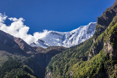 Snowy mountain peak between mountains and trees. View from the  Annapurnas circuit, Himalaya, Nepal Royalty Free Stock Image